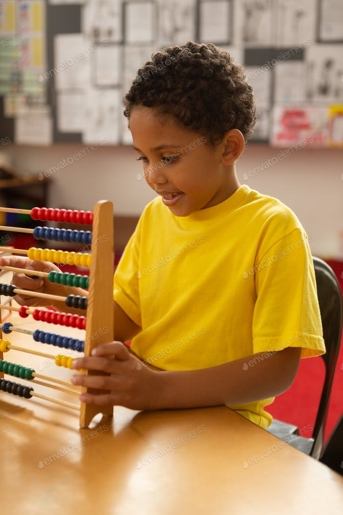 Cute schoolboy learning mathematics with abacus in a classroom at elementary school