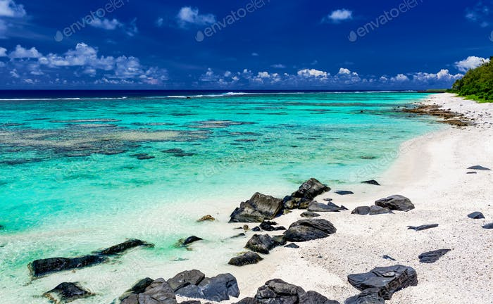 Amazing beach with white sand and black rocks on Rarotonga, Cook