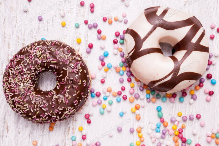 Different type of donuts on white wooden background