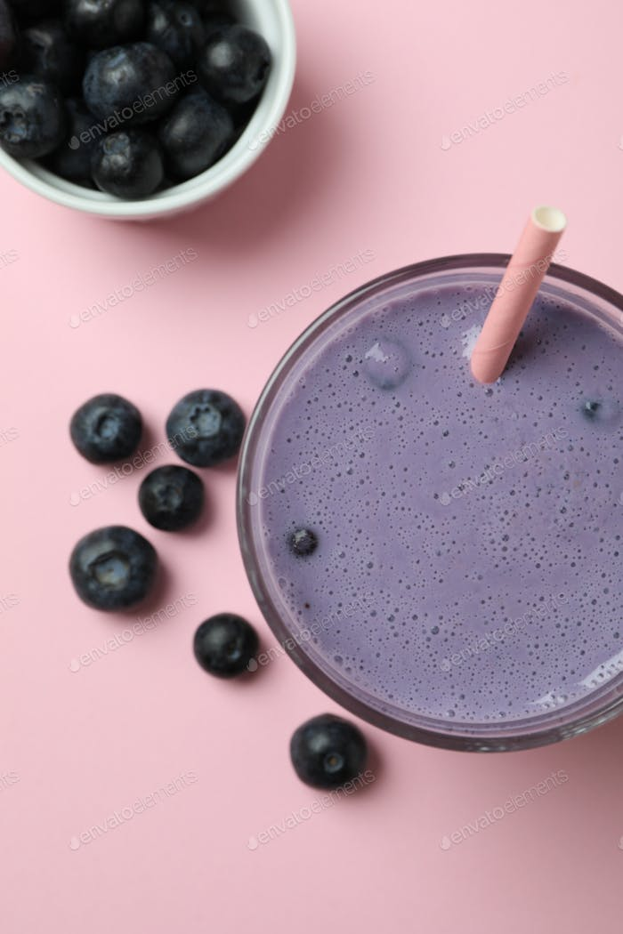 Glass of blueberry smoothie on pink background
