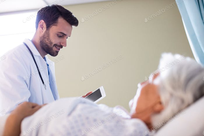 Male doctor discussing medical report over digital tablet with female senior patient in the ward