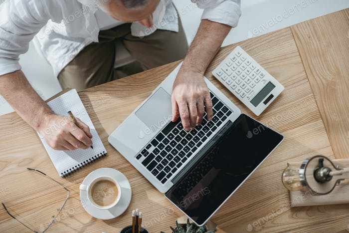senior businessman working on laptop and making notes
