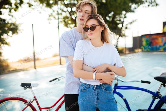 Portrait of young couple dreamily looking aside with red and blue bicycles beside