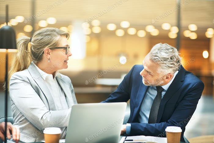 Mature businesswoman shaking hands with a colleague in an office
