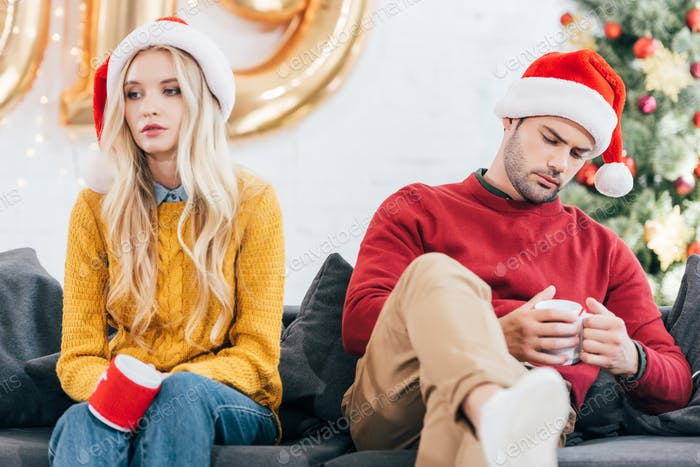 upset couple in bad mood holding cups of coffee and sitting at home on christmas eve