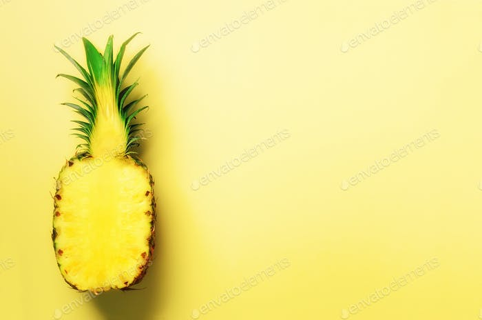 Half of sliced pineapple on yellow background. Top View. Copy Space. Bright pattern for minimal