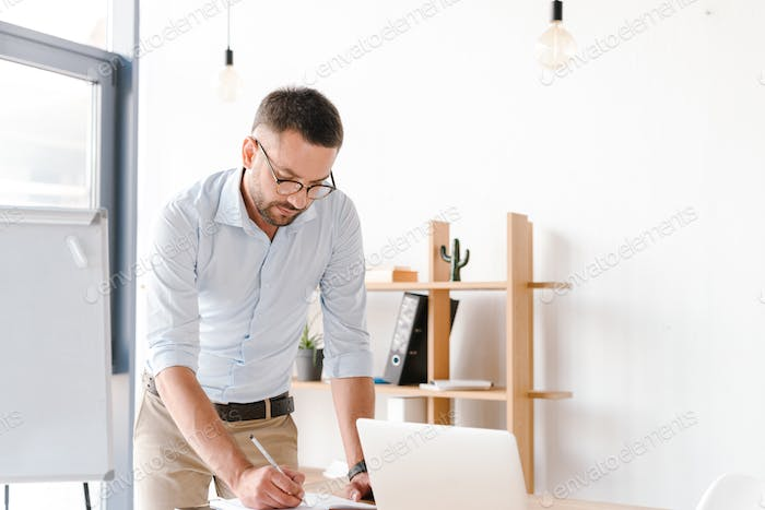 Photo of businessman 30s in white shirt writing down information