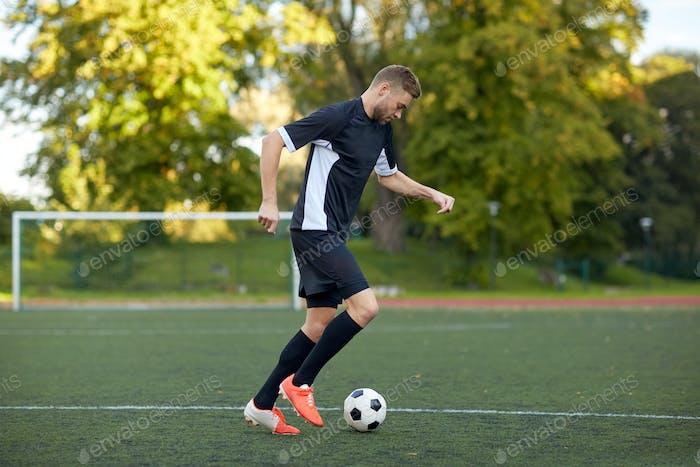 Fußballspieler spielen mit Ball auf Fußballplatz