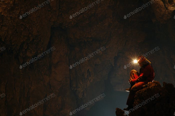 Spelunker resting in a cave