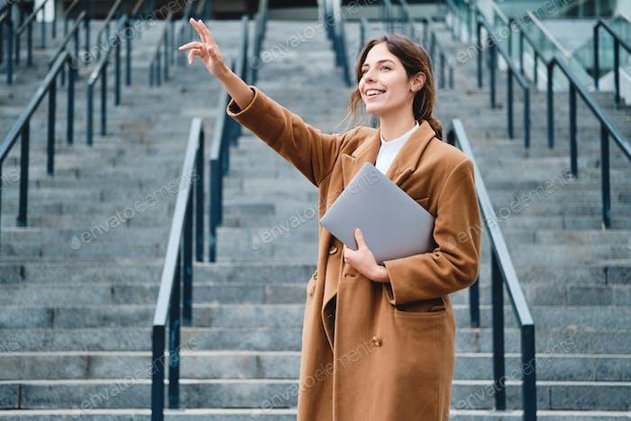 Young smiling casual businesswoman in coat with laptop joyfully waving hand hi gesture outdoor