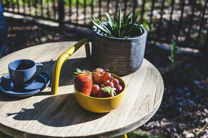 Drink and fruit on a table in the garden.