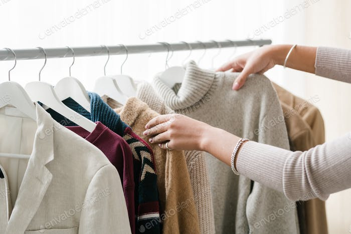 Hands of young female shopper choosing warm knitted and woolen clothes