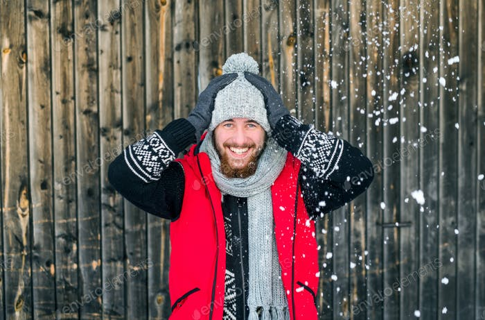 Young man standing against wooden background outdoors in winter.