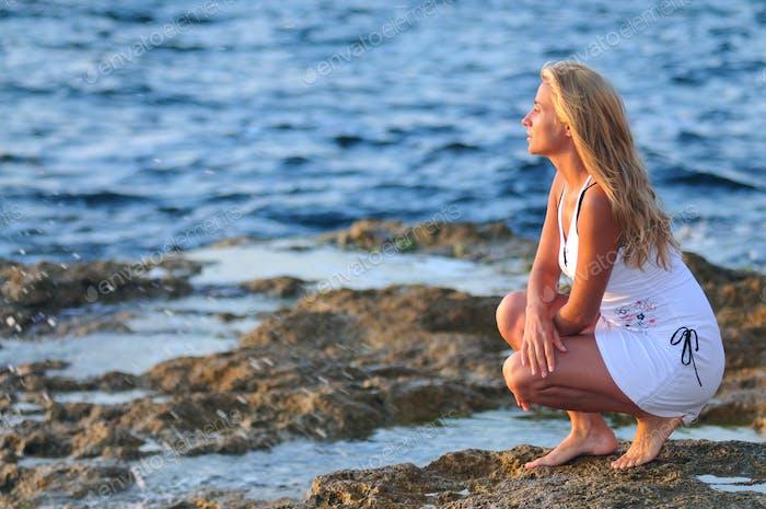 Junge Frau im Bikini stehend auf weißem Katamaran im Meer und lächelnd