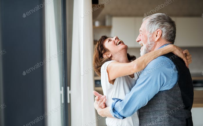 A senior couple indoors at home, laughing and hugging