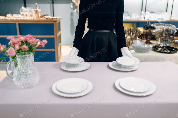 Waitress puts dishes for banquet, table setting