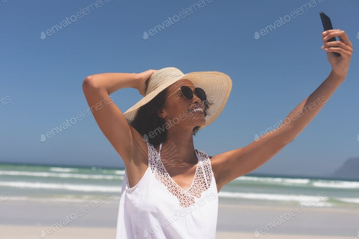 Woman talking selfie at beach on sunny day