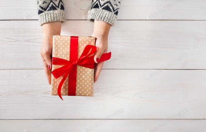 Frauenhände schenken Weihnachtsgeschenk in Geschenkbox