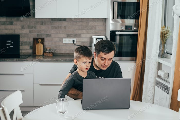 Father working from home with children at kitchen table