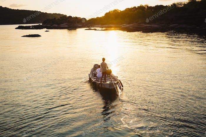 Hochwinkelansicht des Mannes, der bei Sonnenaufgang ein kleines Boot in Richtung einer Insel steuert.
