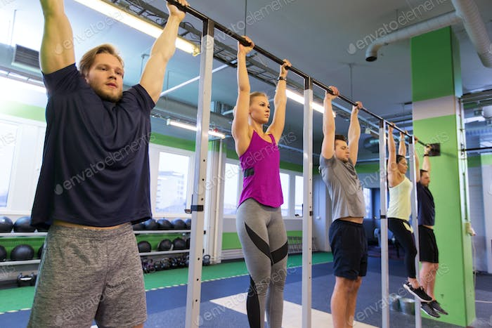 group of people hanging at horizontal bar in gym