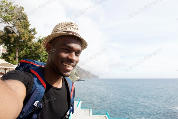 happy young black travel man smiling while taking selfie by the sea