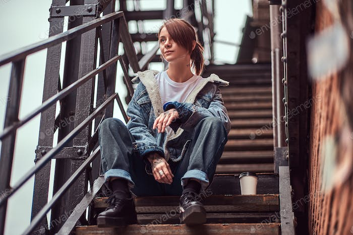 A tattooed girl wearing trendy clothes sitting on stairs outside.