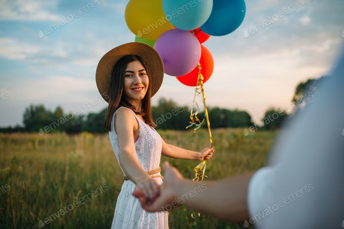 Woman holds bunch of balloons, couple in field