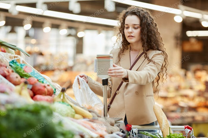 Young Woman Buying Vegetables in Grocery Store