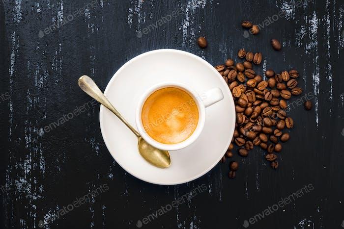 Tasse Espresso Kaffee und Bohnen auf Holztisch schwarz lackiert