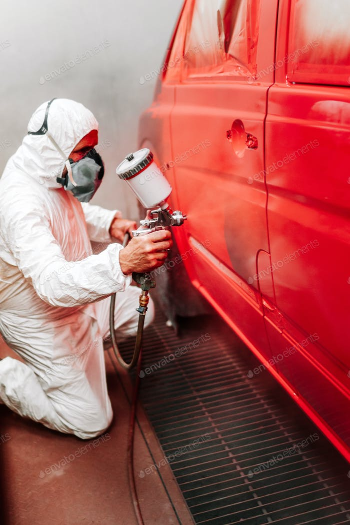 Automotive industry manufacturing details - painter working on applying red paint on a van