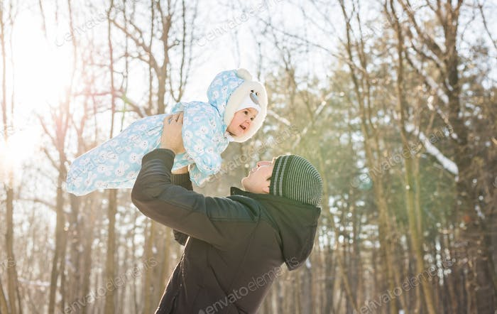 Happy father playing with little child son boy in winter