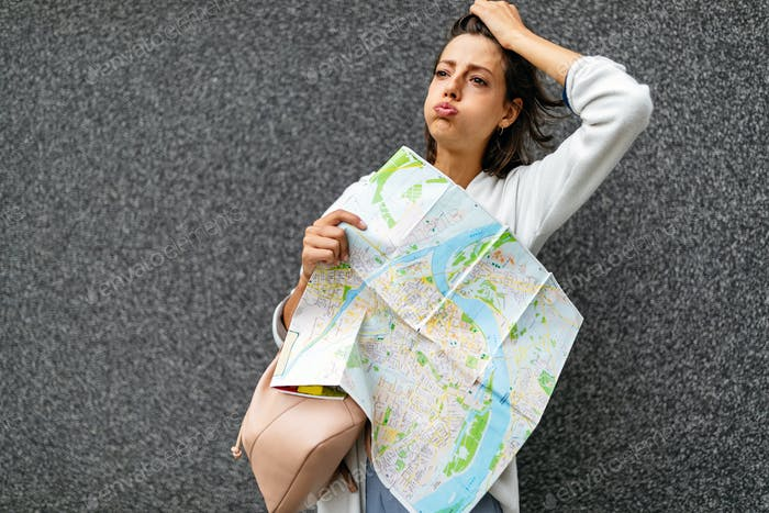 Confused tourist woman on the street looking at a map