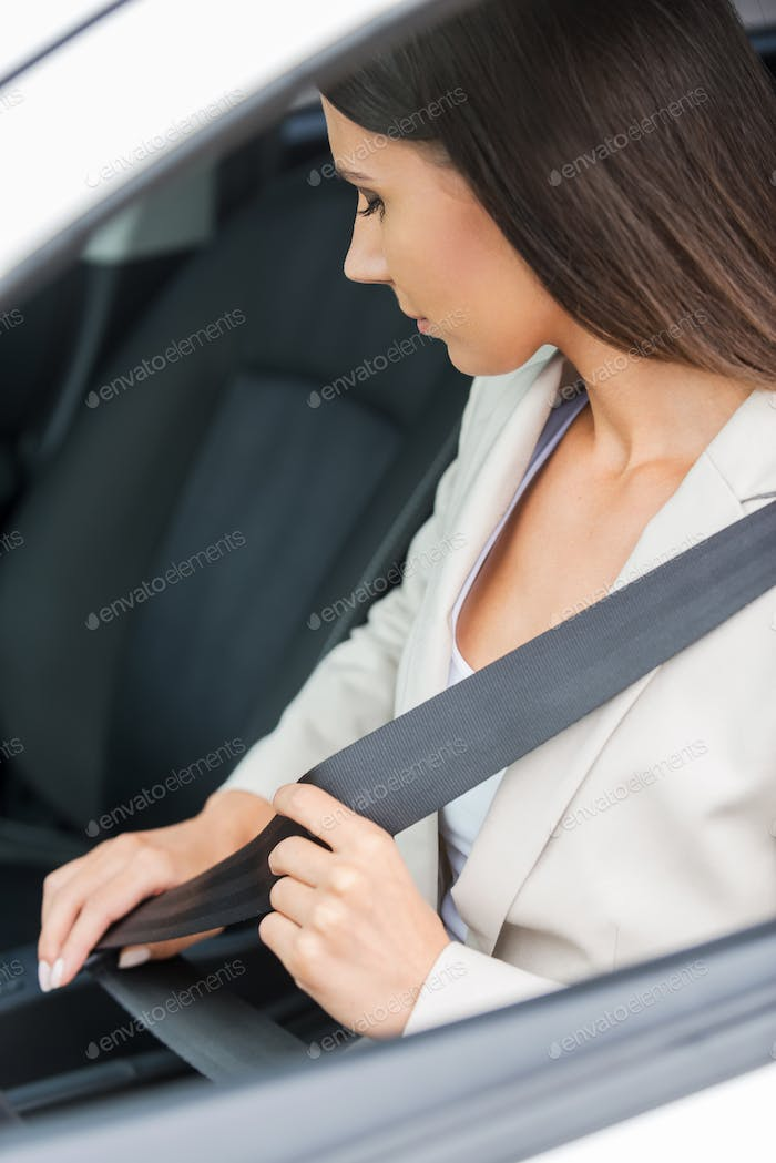Fastening her seat belt. Confident young businesswoman fastening seat belt while sitting in his car