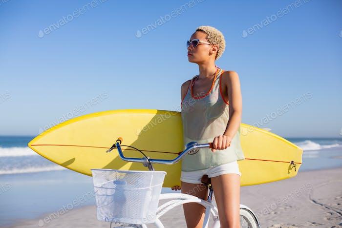 Vorderansicht der Afroamerikanerin mit Surfbrett sitzt auf dem Fahrrad am Strand in der Sonne