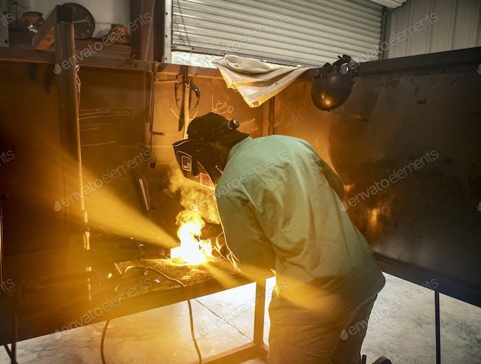 Ein Mann schweißt zwei Metallteile in einer Aufnahme mit einem Lichtbogenschweißgerät zusammen.