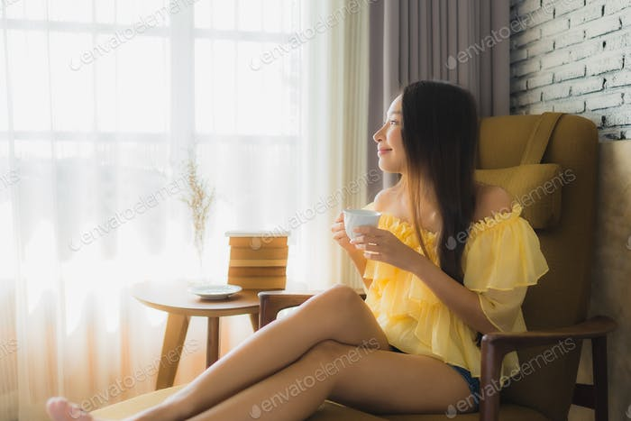 Portrait young asian woman sit on sofa chair and read book with coffee cup