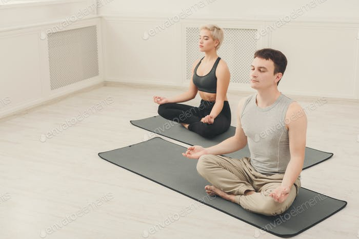 Young couple meditating together in studio