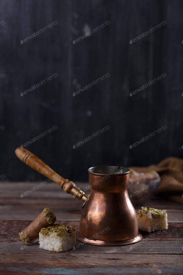 Traditional copper coffee turk or cezve with turkish delights, copy space