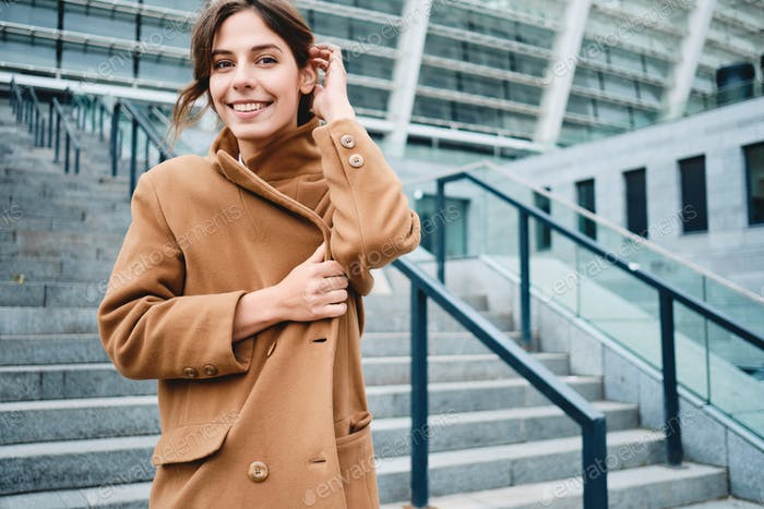 Young positive woman fastening up coat from cold happily looking in camera outdoor