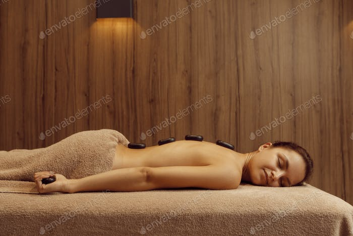 Woman with stones on back lying on massage table