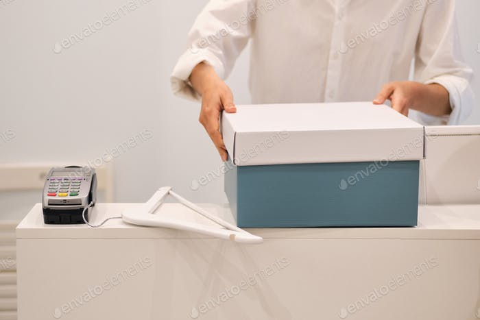 Close up fashion consultant packing clothes in box in store