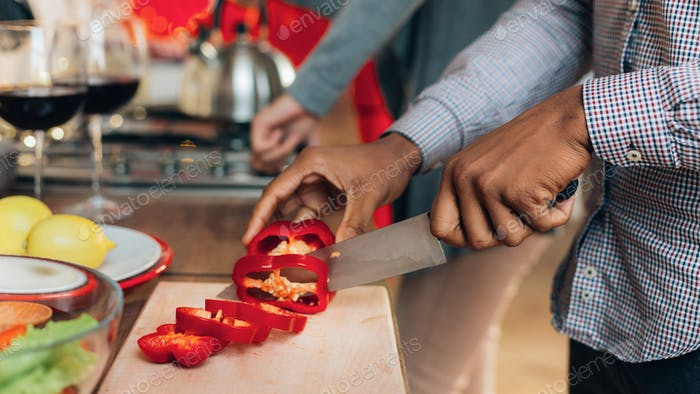 African-american man cutting bell pepper in kitchen