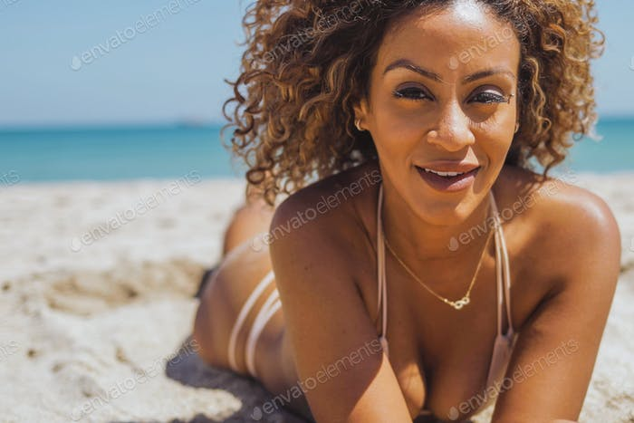 Pretty woman in bikini lying on beach