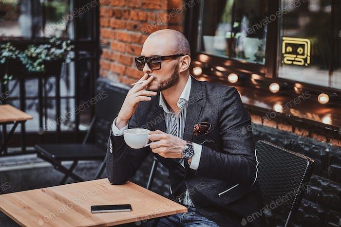 Задуманный человек пьет кофе и курит за пределами кафе