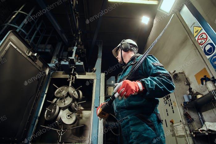Der Mensch arbeitet in der geschäftigen Metallfabrik