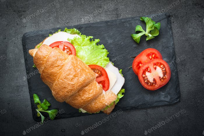 Croissant sandwich with ham, cheese, lettuce and tomato