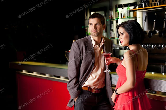 young couple at bar counter talking