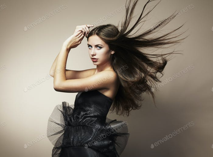 Portrait of young dancing woman with long flowing hair