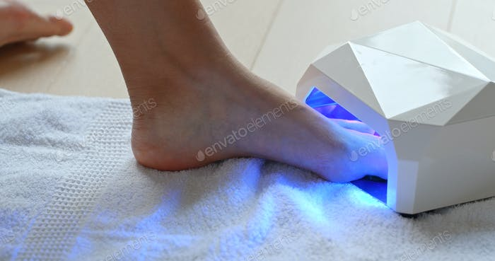 Woman polish her toe nail at home